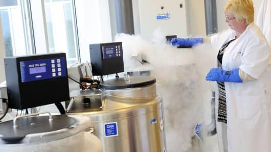 A technician opens a vessel containing women's frozen egg cells.