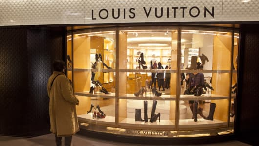 A shopper looks at the window display of a Louis Vuitton store, operated by LVMH Moet Hennessy Louis Vuitton SA.