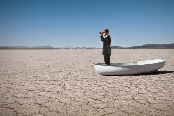 businessman in boat in desert, climate change business, climate change effects