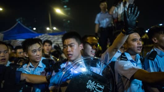 A police officer raises a hand during a protest of pro-democracy demonstrators at Admiralty in Hong Kong, China.