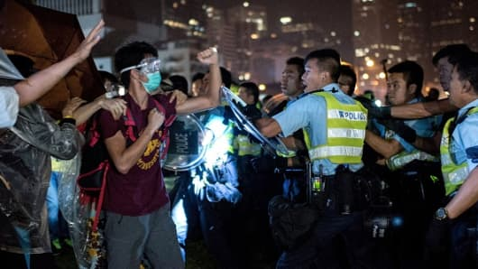 A pro-democracy protester shakes his fist at police officers as they advance in Hong Kong on October 15, 2014.