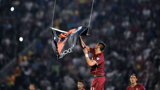 Serbia's Stefan Mitrovic grabs a flag with Albanian national symbols flown by a remotely operated drone during the Euro 2016 group I football match between Serbia and Albania in Belgrade on October 14, 2014.