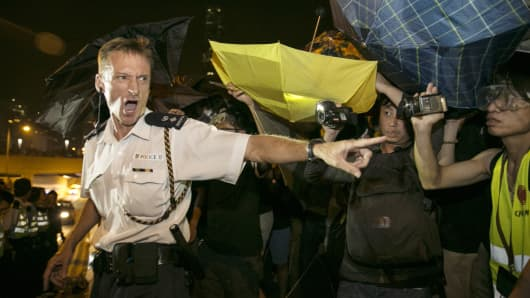 A policeman screams at protesters after scuffles broke out between police and protesters in Hong Kong.