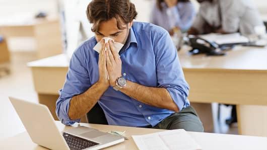 Man blowing nose at work