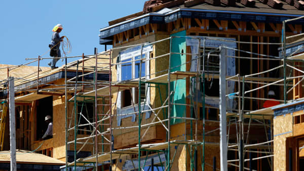 A worker walks on scaffolding at the construction site of a new home in Carlsbad, California.