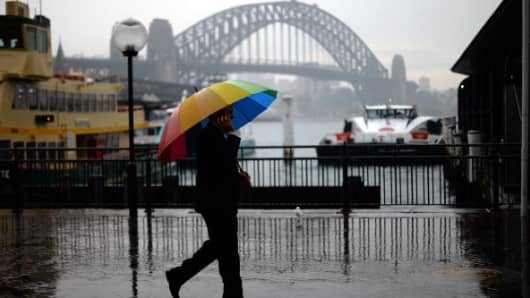 A man uses umberalla to during rain in front of the Sydney's iconic landmark Harbour Bridge on June 25, 2013
