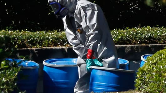 A hazmat worker removes a barrel from The Village Bend East apartment where a second healthcare worker who has tested positive for the Ebola virus resides.