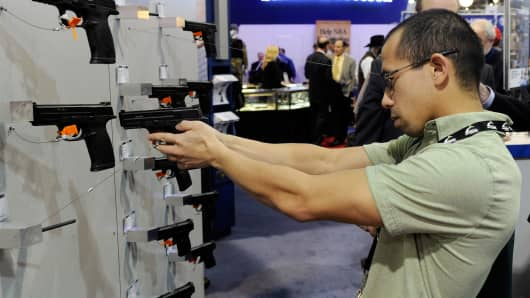 File photo: A man trying out a handgun at the Smith & Wesson booth at the National Shooting Sports Foundation's 33rd annual Shooting, Hunting and Outdoor Trade (SHOT) Show.