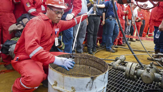A technician takes a sample of crude oil from a well operated by Venezuela's state-owned oil company in Morichal, Venezuela.