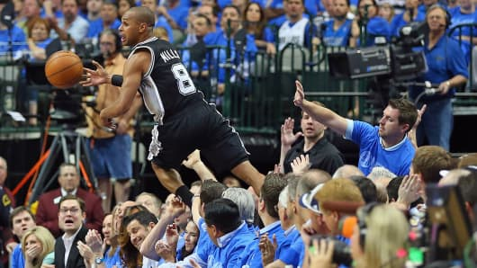 San Antonio Spurs' Patty Mills (8) saves the ball during a game against the Dallas Mavericks during the 2014 NBA playoffs in Dallas.