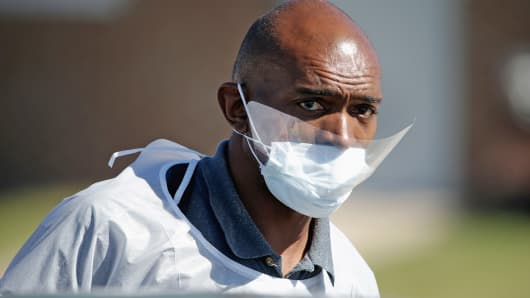 A custodial worker wears a mask and eye protection to guard against the Ebola virus as he prepares to clean Ruth Cherry Intermediate School in Dallas.