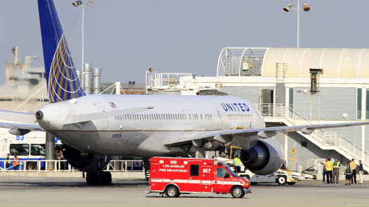 A Los Angeles Fire Department Paramedic truck drives past a United Airlines plane that was diverted to a remote gate after landing at Los Angeles International Airport after a passenger on the flight exhibited flu-like symptoms.