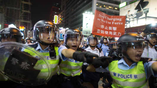 Police shout towards pro-democracy protesters during clashes as they attempt to clear a road in the Mong Kok district of Hong Kong on October 18, 2014.