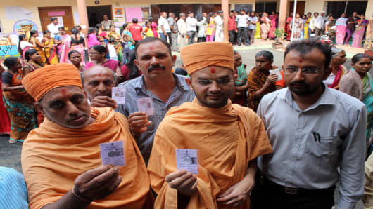Voters showing their voter ID card before casting their vote for assembly election at a polling station on October 15, 2014 in Nagpur,