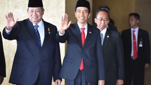 Indonesia President Susilo Bambang Yudhoyono (L) and president-elect Joko Widodo (C) wave to photographers before the inaugural ceremony at the House of Representative in Jakarta on October 20, 2014.