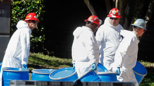 Hazmat workers with Protect Environmental unload barrels in preparation for decontaminating an apartment at The Village Bend East apartment complex where a second health care worker who has tested positive for the Ebola virus resides on October 15, 2014 in Dallas, Texas.