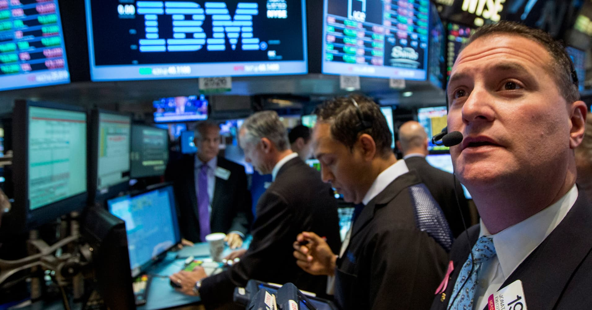 Traders gather at the post that trades IBM on the floor of the New York Stock Exchange, Oct. 20, 2014.