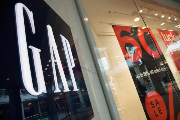 Sale signs in the windows of a GAP store.