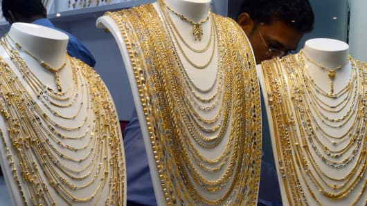 An employee adjusts gold jewellery on display at the global B2B Jewellery and Gem Fair in New Delhi.