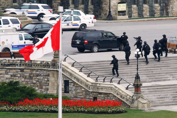 Armed RCMP officers approach Centre Block on Parliament Hill following a shooting incident in Ottawa October 22, 2014.