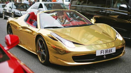 A gold Ferrari drives through the Knightsbridge section of London, Aug. 8, 2014.