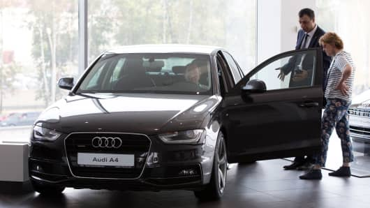 A car dealer assists customers with an Audi A4 automobile at an Audi AG showroom in Moscow, Aug. 2, 2014.