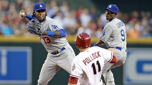 Los Angeles Dodgers' Hanley Ramirez throws the ball over a sliding A.J. Pollock of the Arizona Diamondbacks to complete a double play in Phoenix, May 16, 2014.