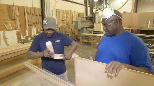 Hardwood Artisan employee training a new hire in the factory.