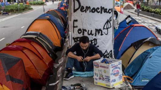 A pro-democracy protester uses a smartphone on the street outside Hong Kong's Government Complex in Hong Kong.