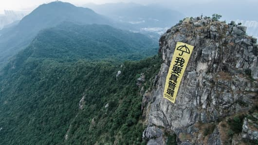 A yellow banner with an umbrella signifying the pro-democracy protest and the chinese text ''I Want True Universal Suffrage'' is placed up the Lion Rock in Hong Kong.