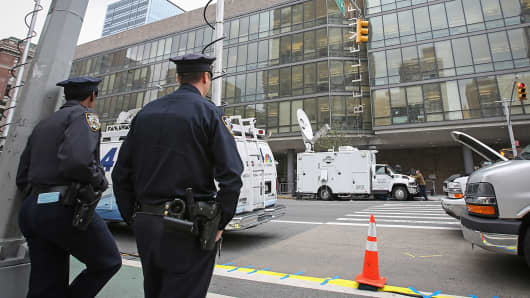 Police officers stand guard as the members of the press work in front of Bellevue Hospital where the doctor who was diagnosed with the Ebola disease and has been kept in quarantine, Oct. 24, 2014, in New York.
