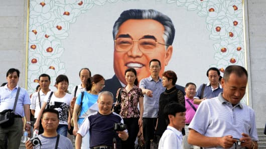 Chinese tourists leave after paying homage to a giant portrait of Kim Il-sung at a square in Rason city in North Korea.