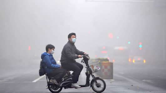 A cyclist wearing a mask rides along a road as heavy smog engulfs China.