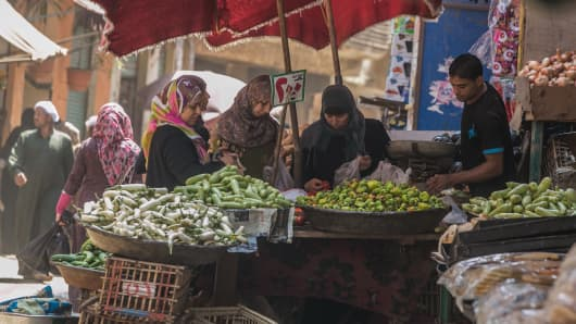 Egyptian women are seen as they buy vegetables in an open-air marketplace in Cairo, Egypt.