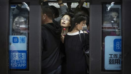 Chinese commuters crowd onto a subway car on the metro during rush hour in Beijing, China.