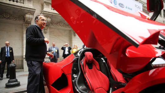 Sergio Marchionne, Chief Executive Officer, Fiat Chrysler Automobiles is viewed next to a Ferrari after ringing the Closing Bell on the floor of the New York Stock Exchange (NYSE) on October 13, 2014 in New York City.