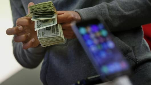 A customer counts cash to pay for two iPhone 6 smartphones during the sales launch at the Apple Inc. store in New York.