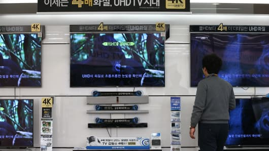 An employee looks at Samsung Electronics Co. ultra high definition (UHD) televisions at the company's digital plaza store in Seoul, South Korea.