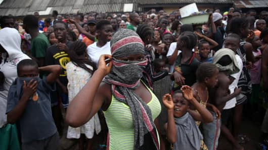 A crowd enters the grounds of an Ebola isolation center in the West Point slum in Monrovia, Liberia.