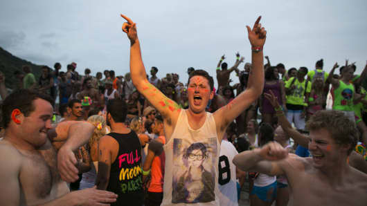 British party goers dance as hundreds of full moon partiers carry on past sunrise on the beach of Haad Rin on August 22, 2013 in Koh Phangan, Thailand.