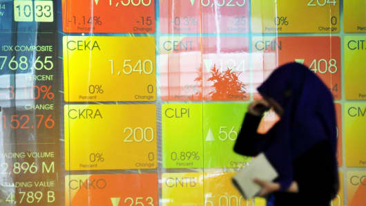A woman walks past the Jakarta Stock Exchange display panel