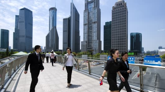 White-collars walk to their lunch break in Pudong business district in Shanghai, China.