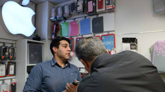 A vendor stands in front of an Apple logo attending to customers in a shop that specializes in iPhone products and it's accessories in Paytakht computer mall in Tehran, Iran.