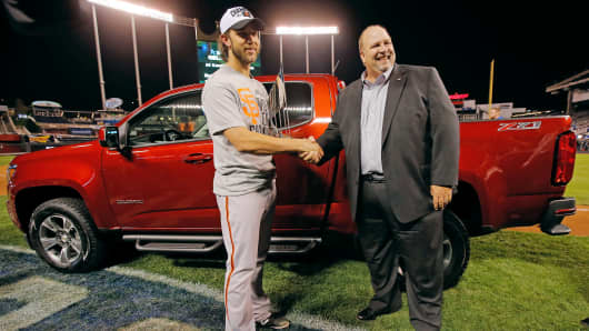 "San Francisco Giants' Madison Bumgarner, left, holds the MVP trophy as he shakes hands with ""Chevy guy"" Rikk Wilde after Game 7 of the World Series in Kansas City, Mo., Oct. 29, 2014."