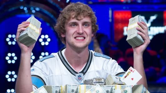 Ryan Riess, 23, a poker professional from East Lansing, Mich, poses with stacks of money after winning the World Series of Poker $10,000 buy-in no-limit Texas Hold 'Em tournament at the Rio Hotel & Casino in Las Vegas, Nevada November 5, 2013.