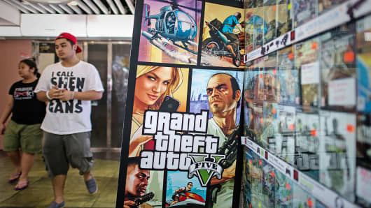 A man walks past an ad for the Grand Theft Auto V video game in Hong Kong.