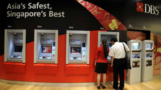 A DBS Group Holdings Ltd. employee assists a customer at an automated teller machine in the company's headquarters at the Marina Bay Financial Centre in Singapore.