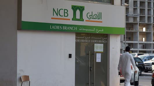 A Saudi man walks in front of a branch of the National Commercial Bank (NCB) in the capital Riyadh.