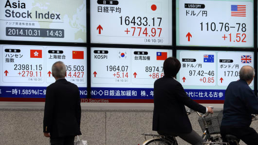 Pedestrians look at an electronic stock board displaying the figure of the Nikkei 225 Stock Average, center top left, and the exchange rate of the yen against the U.S. dollar, center top right, outside a securities firm in Tokyo, on Friday, Oct. 31, 2014.