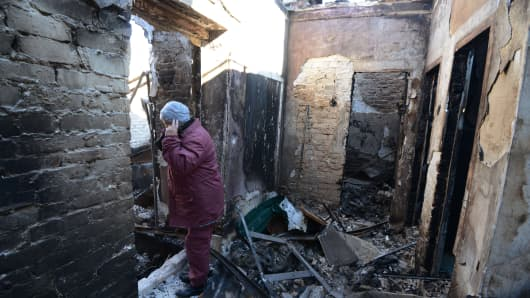 A woman stands in her destroyed home on October 26, 2014 near the Sergey Prokofiev international airport in Donetsk, eastern Ukraine.